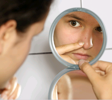 A girl looking on her nose in a mirror