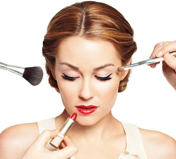 A woman with a lipstick and two brushes near her face