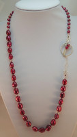 "This exciting necklace radiates passion from the Cherry Red Baroque Pearls, integrated with smaller Red Pearls and .925 Silver balls. Individually knotted on approx 26"" red silk thread, enhanced by the decorative .925 Sterling Silver Clasp"