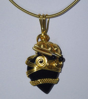 """The ultimate classic look of Black & Gold. Dress it up or down, this Black Onyx Cabachon, woven & coiled in gold coloured wire, will really get you noticed. Suspended on a matching coiled 19"""" necklace with co-ordinating onyx beads. Treat yourself"""
