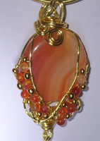"Wear a sunset on your neckline... the warm hues of this orange Agate and Carnelian pendant radiates any skin tone. The cabachon is framed in golden coloured panels and carnelian beads, suspended from an integrated co-ordinated 18.5"" necklace"