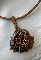 "Rich and dark best describe this mystical pendant, elegantly hung from a matching 19.5"" necklace. A rich brown Agate encompassed in bronze coiled and woven wire, with the stunning deep red hues of Garnet. A Fantastic piece."