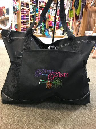 A large, multi-pocketed, durable bag with an embroidered logo from your favorite knitters' haven!