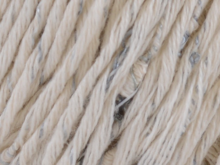 This textural yarn comprises a plied cotton yarn wrapped by a strand studded with mini cocoons in tonally-coordinated colors reminiscent of beaches and the sea.