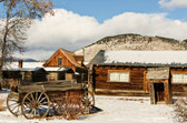 Old Wagon Sits Among Buildings In A Montana Ghost Town In The Winter Photograph