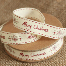 Merry Christmas 3M Ribbon with Snowflake  Why not make this Christmas that little bit extra special. Decorate your gifts with this beautiful high quality ribbon, the ribbon is white with red stitching along each edge and the words 'Merry Christmas' running in red along the middle, separated by a grey and red snowflake.  The length of this is 3m-long ribbon to a wrapped present, or just as a decorative touch around the house or hampers.  The ribbon is in canvas material