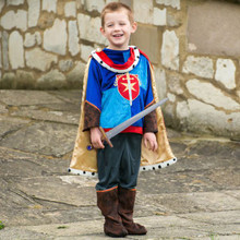 Prince   This Medieval Prince has a royal blue tunic richly appliquéd and embroidered with a shield and sword emblem. The grey trousers have mock leather over boots. The style includes a fur edged cloak with a jewel fastening and golden lining and is complete with a sword fit for a Prince! Available in sizes 3-5 years,