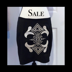 Midi/mini skirt. If you wear it on your hips, it falls closest to your mid thigh. Gorgeous applique that is a brushed gold, slight sliver . Black skirt, zips back. Size Large. Fits around a size 8/10