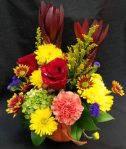 A great mix of fall flowers in this ceramic pumpkin.