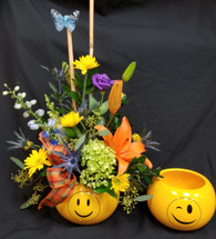 Per availability, emoji container  may be different from one shown. Colors and style of flowers will vary to season and whats available.   Here's a great way to show someone your thinking of them!  Who doesn't love Emoji's!!     LOCAL DELIVERY ONLY