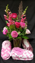 "October is Breast Care Awareness Month. We will Donate 10% of our ""pink"" sales!  That means 10% of this floral arrangement will be donated. Stop into our Shop and check out our other items including the Snoozie Slippers shown in this photo. Thank you for all your support!"
