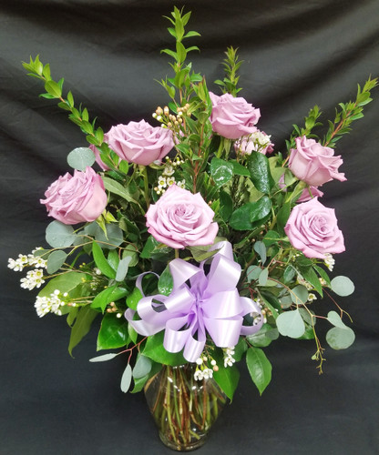 This stunning dozen Lavender Roses in a vase with upgraded greenery (eucalyptus & ruscus) with premium filler such as Wax Flower or Limonium