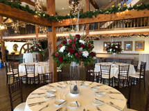 This is a stunning Reception Table Centerpiece, With red roses, red Gerber daisy's, pine cones, Alstromaria, white cremons, white twigs, Monte casino, winter greenery. Perfect for a Winter wedding! Comes with a Rental LED light to give it that glowing look! Starting at $175.00