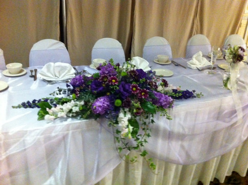 A beautiful mix of purple hydrangea, lisianthus, stock, delphinium, ivy, poms Starting price is $85.00