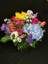 Compact style vase with a bright and colorful mix of seasonal spring flowers. Great way to brighten anyone's day up!