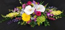 Adorn the table with this beautiful long and low centerpiece to include lilies, gerbs, roses, alstro, poms and other spring flowers. Upgraded for a fuller and more plush look