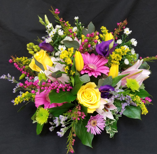 This round centerpiece in a low dish, perfect for a table  includes tulips, snap, gerbs, poms and other spring flowers for the table. Upgraded for a fuller and plush look.
