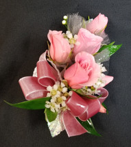 Medium Pink spray roses with a pink ribbon and natural greens