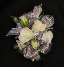 White roses with a lavender/iridescent ribbon with pops of baby's breath with added lavender gems