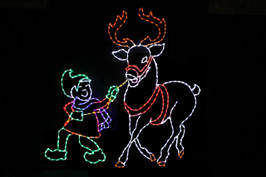 Green LED elf with a red coat and purple scarf guiding a white reindeer with red antlers