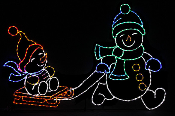Two LED snowmen adorn in colorful hats, scarves and mittens; one snowman is pulling the other on a red sleigh