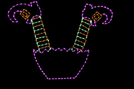 Purple LED Witches dress with green and yellow legs and red shoes sticking up in the air from the ground