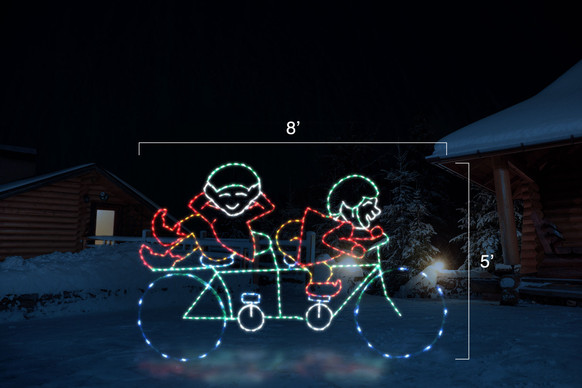 "Animated red and green LED light display of two elves riding a bike  with dimensions 8"" by 5"""