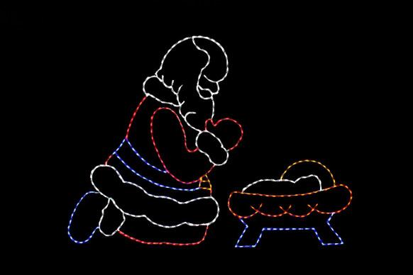 Red, white, blue and yellow LED Santa praying over a red, white, blue and yellow baby Jesus