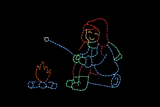 LED light display of a boy dressed in red, green and blue sitting on a blue log roasting a marshmallow over a fire with red flames and blue logs