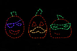 LED light display of three jack-o-lanterns, one has a purple eye patch, one has a yellow mustache, and one has a green eye mask