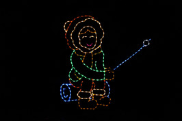 Green, red and yellow light display of a girl sitting on a blue log roasting a marshmallow with a blue marshmallow stick