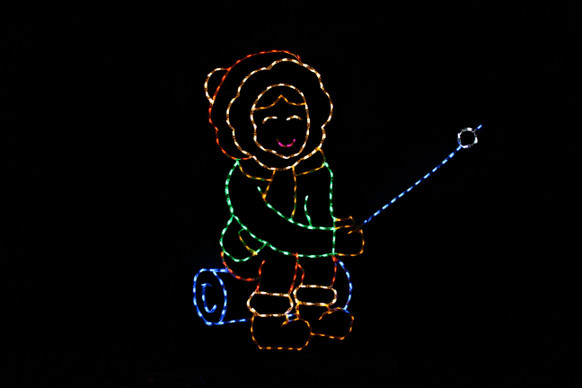 Green, orange and yellow light display of a girl sitting on a blue log roasting a marshmallow with a blue marshmallow stick