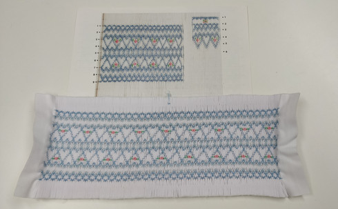 Sweetheart Smocking plate by Ellen McCarn, A ready smocked insert using design II mocking plate, Pleated and smocked on the full width of white imperial broadcloth, Insert is 26 cm from smocked edge to smocked edge but can be spread a little, Smocked in the suggested two shades of blue colours, Full depth of fabric is 11 cm
