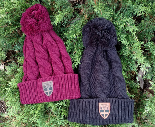 Cooler temperatures will be here before you know it.  This chunky, cable knit, pom pom hat with die cut leather patch will keep you warm.   One size fits all.  Your choice of maroon or black.