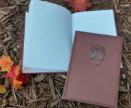 Maroon journal debossed with the Shattuck-St. Mary's Shield. Mid-size notepad and memo book with 128 pages, perforation along the spine and smooth soft texture cover. Measures 6 x 8.5 inches.