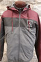 Soccer hooded full zip jacket. Maroon and charcoal , 100% polyester, embroidered left chest logo. Mesh hood lining, zippered side pockets, elastic at waist.