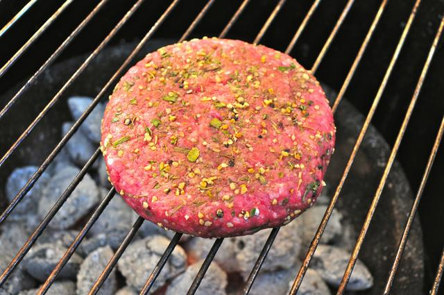 uncooked beef patty burger with french seasonings on grill