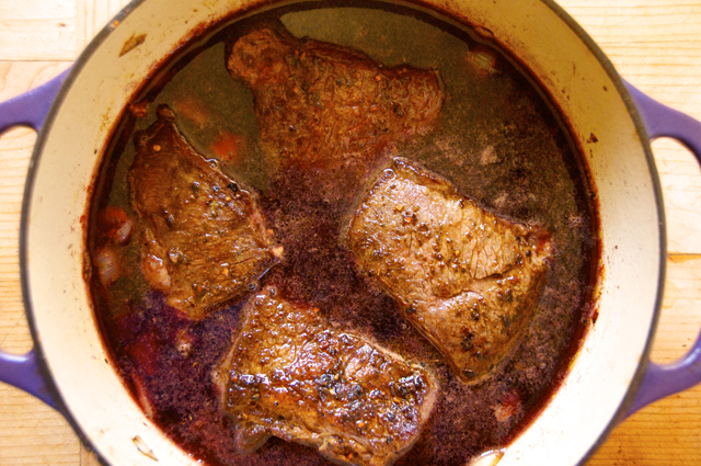 pour red wine and broth with boneless short rib in dutch oven