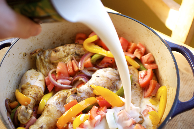 pour coconut milk in dutch oven filled with chicken and chopped vegetables