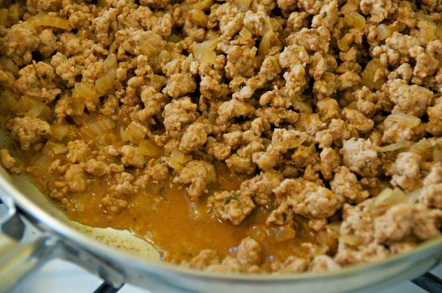 cooking ground turkey with meat juice in pan