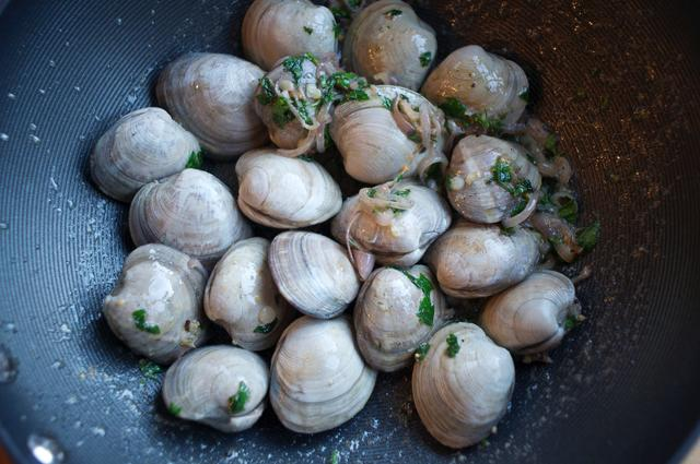 clams coated in white wine with shallots and parsley in a cooking pot