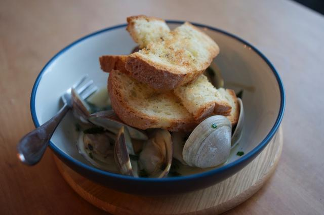 bowl full of steamed clams in white wine with toasted bread