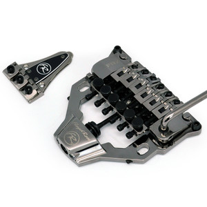 Floyd Rose continues its legacy of innovation with the brand new surface-mounting FRX Tremolo System for Les Paul, SG, and Flying V-style guitars. The FRX is a direct swap for the Tune-O-Matic and stopbar type bridge system, using the existing mounting stud holes and requiring no routing whatsoever. The locking nut mounts behind your guitar's existing nut, in place of the truss rod cover. The FRX locking nut has mounting holes on the left and right; only two wood screws have to be installed to mount the nut. *NOTE: On some Les Pauls, particularly LP Customs, the neck angle is not sufficient to allow the FRX to work without slight modification to the body. The receiving portion of the spring tension transfer rod on the base plate extends slightly below the bridge and may rest on the body unless a tiny channel is routed.