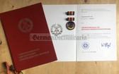 ag020 - c1987 Verdienstmedaille der DDR with award cert and folder - VM Volksmarine Navy officer