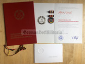 ag021 - c1982 Verdienstmedaille der DDR with award cert and folder - invitation to the award ceremony in Dresden