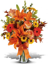 A mix of fresh flowers such as Asiatic lilies, Viking spray chrysanthemums, roses and a miniature gerbera - in shades of orange and yellow - is arranged with preserved oak leaves in a clear glass vase adorned with an orange satin ribbon.