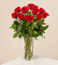 One Dozen Fine Long Stem Roses is a classic expression of love and sweet affection!  Our finest red roses arrive accented with lush greens and baby's breath, beautifully arranged in a clear glass vase, to make this a day they won't soon forget.