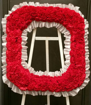 "This custom made Ohio State ""O"" can be created to honor your Buckeye fan.  The red carnations are trimmed in a light gray ribbon and attached to a wooden easel for easy display."