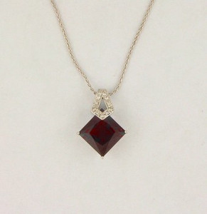 Garnet and Diamond Pendant. 18 KW Gold. .06 CTTW.