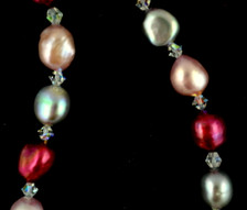 22 inch dyed red, pink and gray freshwater pearl and quartz necklace, 9.5 mm to 10.5 mm, with sterling silver clasp. Strand is individually knotted between each pearl for added security.